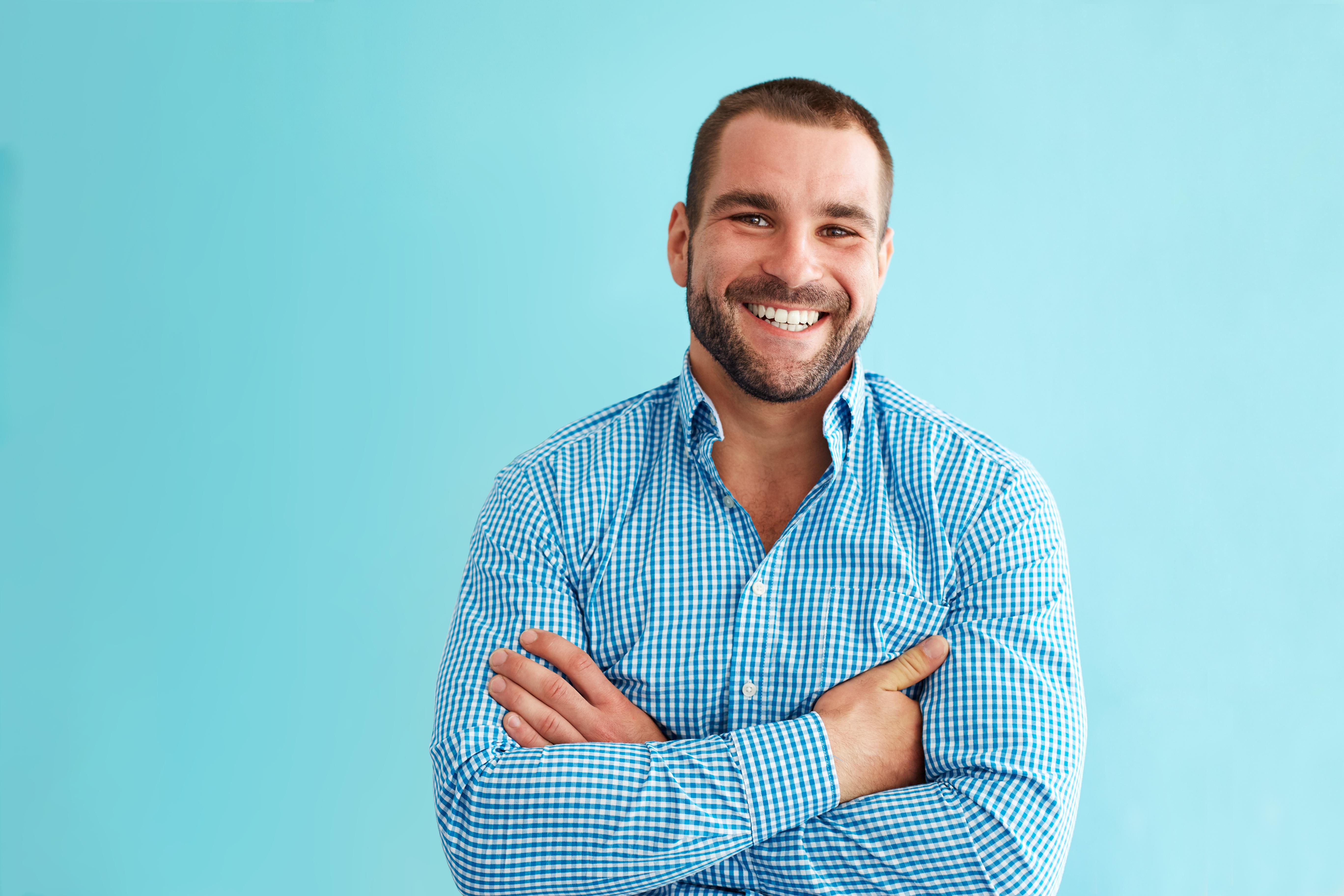 imagem de homem branco sorrindo com fundo azul claro