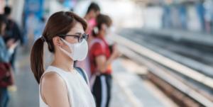 mulher de roupas brancas e óculos usando máscara em estação de trem