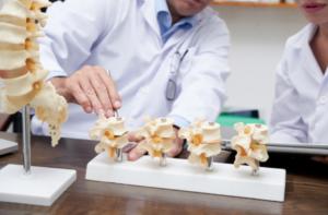 imagem de um médico explicando sobre fraturas na coluna para paciente através de um modelo