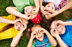 imagem de crianças deitadas com as mãos sobre os olhos formando um círculo