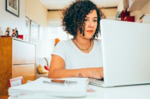mulher de roupas brancas sentada a uma mesa teclando em seu laptop
