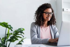 mulher negra de óculos sorrindo enquanto está sentada a uma mesa usando um computador