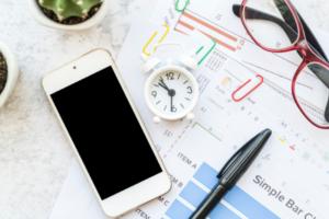 imagem de uma mesa com um celular, gráficos em papel,par de óculos, uma caneta preta e um alarme