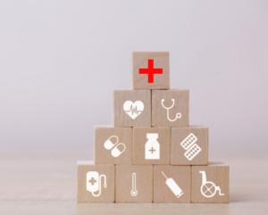 imagem de pequenos cubos de maneira com desenhos relacionados à medicina empilhados sob uma mesa