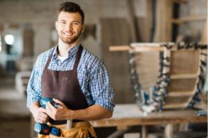 homem usando camisa xadrez azul e avental marrom sorri enquanto segura uma furadeira em meio a uma cpnstrução