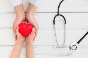 em uma mesa branca duas pessoas esticam seus braços segurando um coração de borracha na cor vermelha e ao lado se encontra um estetoscópio