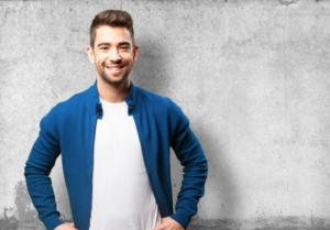 homem de casaco azul sorrindo de costas para parede cinza