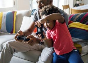 pai e filho jogam videogame juntos sentados ao sofá de sua casa