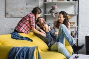 familia formado por homem, mulher e filha brincam e dão risada em cima de um sofá amarelo