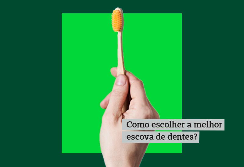 Mão de pessoa segurando uma escova de dente com cerdas laranjas em um fundo verde escrito como escolher a melhor escova de dentes?