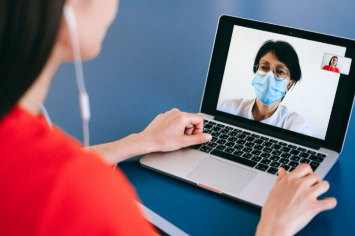 mulher de camiseta vermelha conversando por videochamada com mulher de máscara